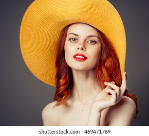 Sexy young red-haired woman in a hat with red lips