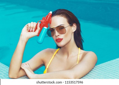 Sexy young spy woman holding water gun in swimming pool, retro style