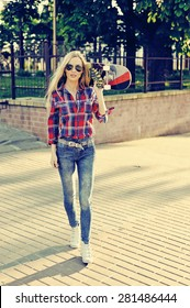 Sexy young stylish woman model girl in bright modern clothes and sunglasses. Walking with skateboard in the street