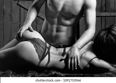 Sexy young undressed sensual woman with beautiful straight body in red lace erotic lingerie lying near muscular man touching buttocks posing indoor on wooden background, horizontal picture