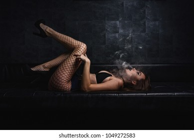 sexy young vaping girl in black Lingerie. Girl blowing vape. Vapor concept.