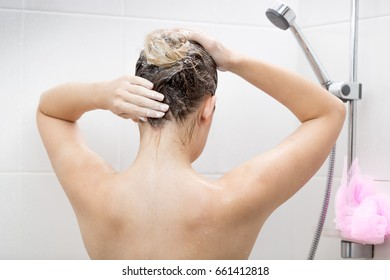 Sexy young woman applying hair lotion in shower