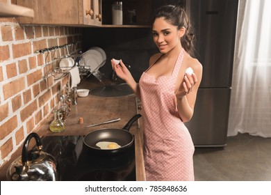 sexy young woman in apron holding eggshell and smiling at camera while frying egg at kitchen
