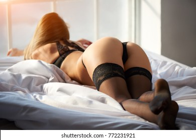 Sexy young woman, bed. Attractive girl in black lingerie.