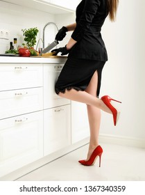 Sexy young woman in black dress and red shoes with knife preparing dinner in the kitchen