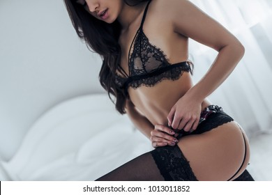 Sexy young woman in black lace lingerie and stockings is standing near white bed.