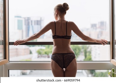 Sexy young woman in black lace lingerie standing next to bedroom window.