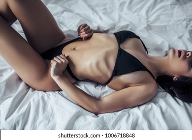 Sexy young woman in black lingerie is lying on white bed.