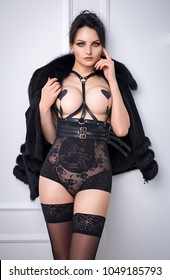 Sexy young woman in a black lingerie and black fur coat