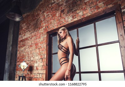 Sexy young woman in black sensual lingerie. Girl posing on brick wall in studio.