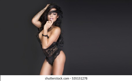 Sexy young woman in black sensual lingerie. Girl posing on black wall in studio.