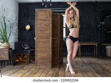 Sexy young woman in black swimsuit posing in the stylish interior of the Studio.