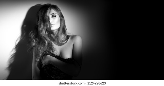 Sexy Young Woman black and white portrait. Seductive young woman in lingerie in darkness. Glamour lady with long hair posing in spotlight. Border design. Wide angle
