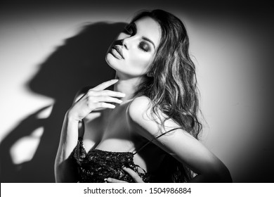 Sexy Young Woman black and white portrait. Seductive young woman in lingerie in darkness. Glamour lady with long hair posing in spotlight. Gorgeous seductive model girl with long hair b&w