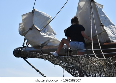 A sexy young woman with brown hair, a black shirt and hotpants works in the sails of a ship on a warm and sunny spring day in Toronto-Canada.