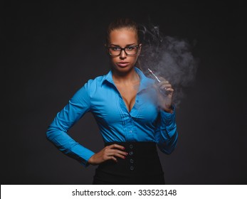 sexy young woman in casual office wear vaping e-cigarette against dark gray background