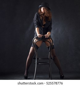 Sexy young woman dancing with a chair
