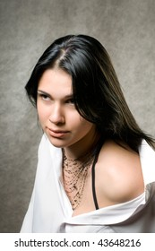 Sexy young woman with dark hair in a man's white shirt,  naked shoulder.