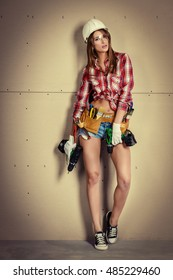 Sexy young woman doing repairs at home. Portrait of the attractive female construction worker. Building, repair concept.