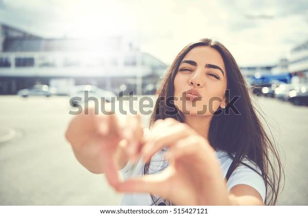 セクシーな若い女性は、指でハートの形を作るキスをしながら、都会の広場の外に立ち、口を大げさに開く