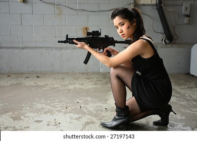 A sexy young woman with a gun.