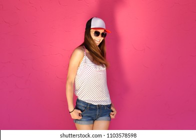 Sexy young woman in hip hop style clothes and sunglasses posing against a pink wall background