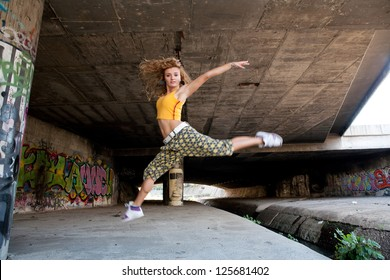 Sexy young woman in hip hop style, dance front colorful graffiti.