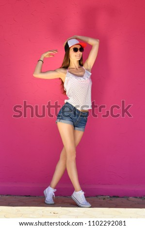 Sexy young woman in hip hop style clothes and sunglasses posing against a  pink wall background 1e15639939b