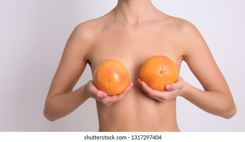 Sexy young woman holding grapefruits near her breasts on light background. Erotic concept