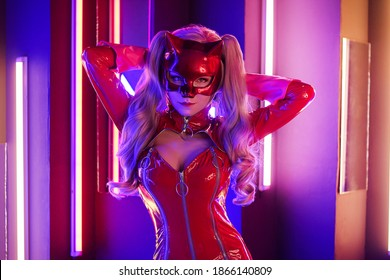 Sexy young woman in leather red dress with cat mask in neon lights holding her hair portrait