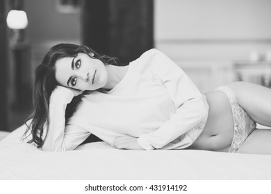 Sexy young woman in lingerie posing on the bed. Brunette girl with white panties and pyjama in her bedroom. Black and white photograph.