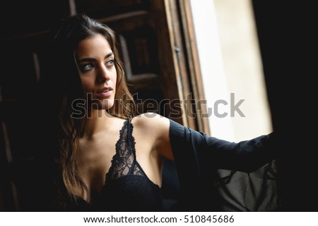 Sexy young woman in lingerie standing near a window in her bedroom.  Brunette girl wearing 68f15f723