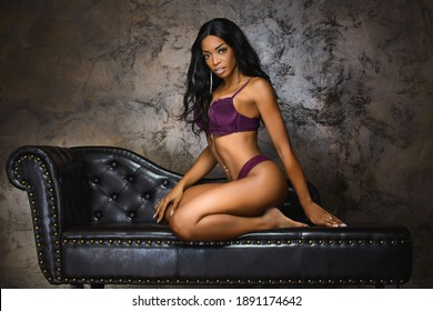 Sexy young woman with long legs sitting on a dark brown leather