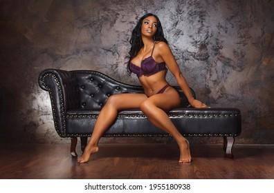 Sexy junge Frau mit langen Beinen auf dunkelbraunem Ledersofa