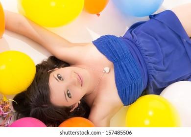 sexy young woman lying on floor among balloons