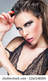 Sexy young woman with makeup in black erotic lingerie. Studio shoot