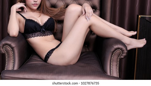 sexy young woman model in sexy black lingerie posing on armchair