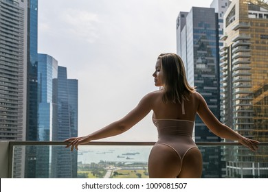sexy young woman in an open body is standing on the balcony with her back on the background of the city of Singapore...