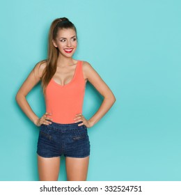 Sexy young woman in orange shirt and jeans shorts standing with hands on hip, smiling and looking away. Three quarter length studio shot on teal background.