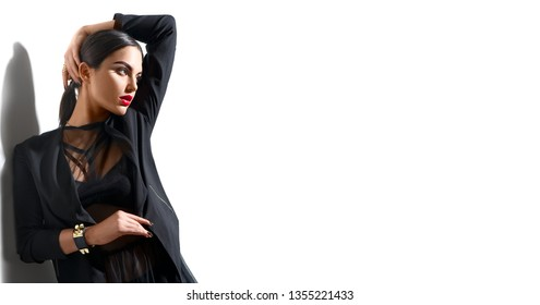 Sexy young woman portrait, isolated on white background. Seductive brunette model girl in black sexy clothes, fashion accessories, bright makeup posing in studio. Beauty female, perfect glamour makeup