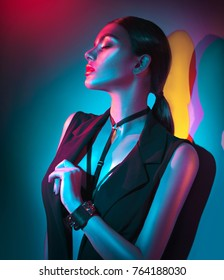 Sexy young woman portrait, on colorful background. Seductive brunette model girl in black sexy clothes, fashion accessories, bright makeup in neon light. Clubber, night life