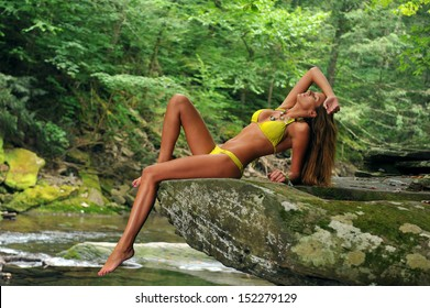 Sexy young woman posing in designer bikini at exotic location of mountain river with green water, rocks and forest in background