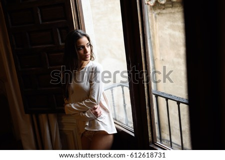 Sexy young woman in pyjama and white panties standing near a window in her  bedroom. fd9fd6e9c