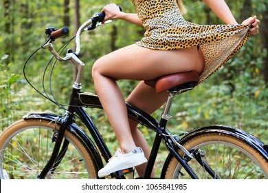 Sexy young woman is riding on a bike in summer forest
