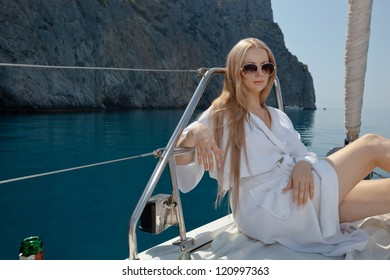 sexy young woman sitting on the yacht in sunglasses and a in dressing gown