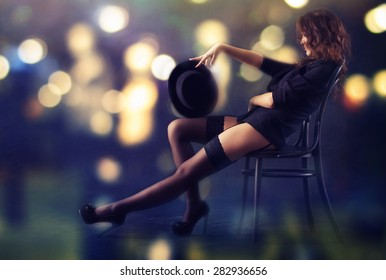 Sexy young woman sitting on a chair against a background of bright lights at night.