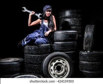 Sexy young woman sitting on wheels with a big wrench over black background
