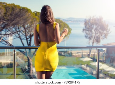 Sexy young woman standing on the balcony with beverage and looking at the view