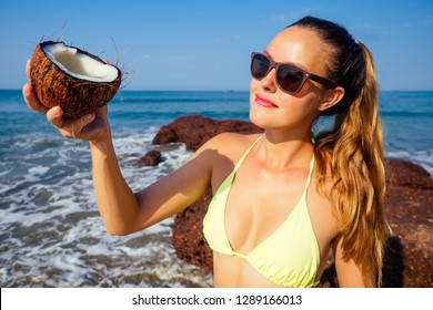 sexy and young woman in a stylish bikini swimsuit holding a coconut on the ocean tropical paradise shore. sexy perfect fit model in water with coconut milk drops pouring coco nut water