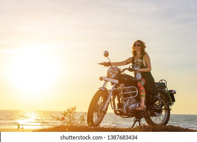 A sexy young woman in sunglasses sits on a black chrome motorbike. Hipster girl on a motorcycle against the sunset. The concept of women's independence.